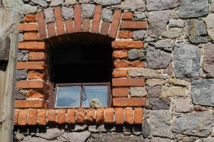 Ferienwohnung auf dem Feldsteinhof - Feldsteinmauer mit ziegeleingefasstem Fenster